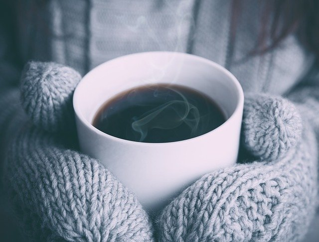 a woman holding a cup of coffee in winter